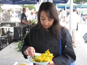 Helena buying zucchini blossoms at the Farmers' Market