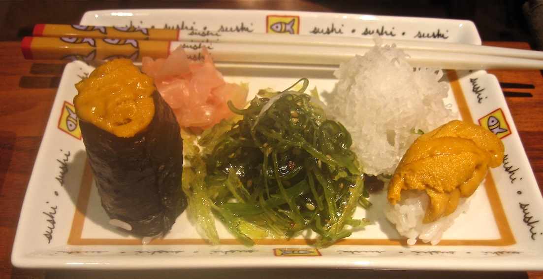 individual sushi plate with seaweed salad, daikon, uni, ginger, wasabi and chopsticks