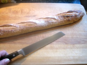 baguette on cutting board with serrated knife