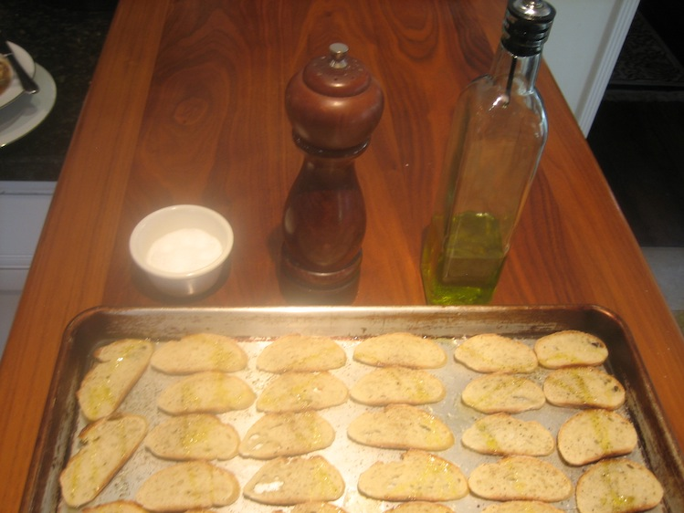 Crostini on baking sheet with olive oil, pepper mill, and salt