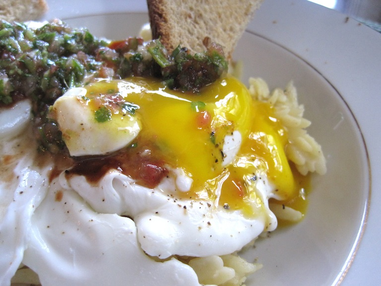 Breakfast - Poached Eggs over Orzo with toast being dipped into yolk