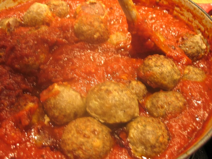 meatballs being added to the pasta sauce