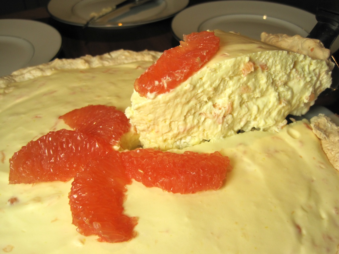 Cutting a piece of grapefruit pie with coconut meringue crust