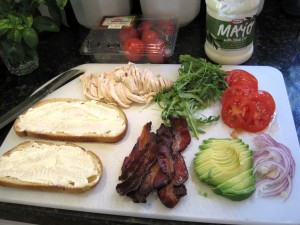 ingredients for a super club sandwich on a cutting board