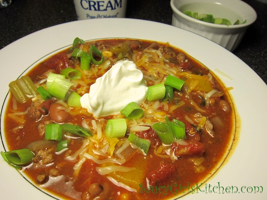 Homemade Chili topped with Cheese, Scallions and Sour Cream