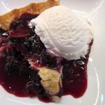 Slice of Warm Blueberry Pie with Vanilla Bean Ice Cream