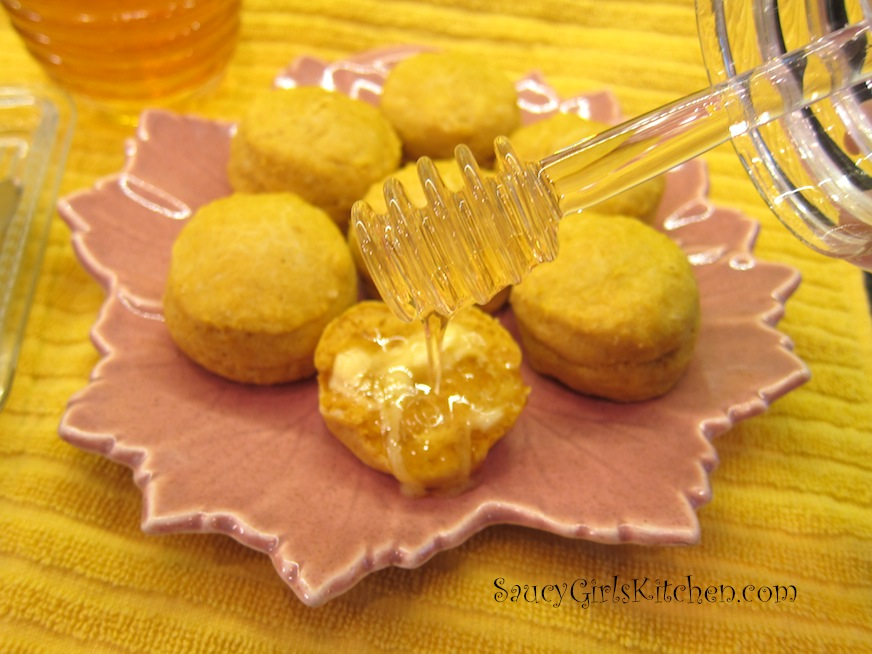 Pouring honey on a buttered pumpkin biscuit